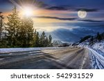 day and night concept of winter mountain landscape. road goes down to village through spruce forest covered with snow on fresh frosty day - stock photo