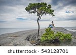 Small photo of Solitude and Loneliness expressed by a young man, the sea, and a lonely tree