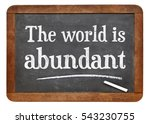 Small photo of The world is abundant - white chalk text on a vintage slate blackboard