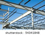 the structural steel structure of a new commercial building against a clear blue sky in the background - stock photo