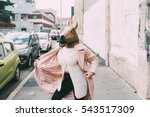 Small photo of Woman wearing horse mask dancing outdoor in the city - strange, absurd, carnival concept