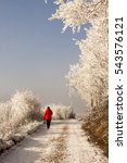Small photo of A woman in a red winter garb walking in the snow path.