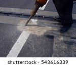 Small photo of Road worker works with an air hammer