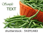 Fresh green beans in orange wicker basket on white background with copy space.  Macro with shallow dof. - stock photo