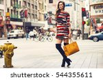 Small photo of Fashionable brunette woman in a nice dress, over knee boots, yellow handbag walking in the street. Fashion spring summer autumn photo