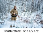 Small photo of Hunter man dressed in camouflage clothing in the winter pine forest. Armed with a rifle