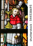 Small photo of GHENT, BELGIUM - DECEMBER 23, 2016: Stained Glass window depicting an Altar Boy holding a Candelabrum in the Cathedral of Saint Bavo in Ghent, Flanders, Belgium.