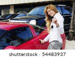 happy woman showing key of new red sports car - stock photo