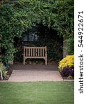 Small photo of Small Park Bench in Ivy Alcove behind green lawn