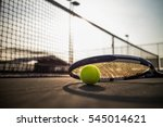 Tennis ball and racket on hard...
