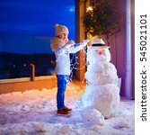 young kid making snowman in... | Shutterstock . vector #545021101