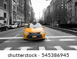 Small photo of New York City taxi in yellow color in the traffic light with building and car in background