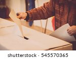 a person casts her ballot... | Shutterstock . vector #545570365