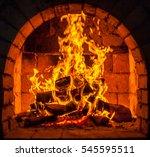 a fire burns in a fireplace. | Shutterstock . vector #545595511