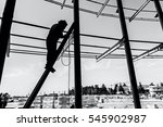 Silhouetted industrial shot of construction worker who is using the wooden ladder to welding metal frame. - stock photo