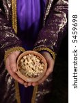 Small photo of Wise man arrayed in purple cloak embroidered with metallic gold thread, his hands holding an ancient clay pot filled with hojari frankincense from dhofar region Oman. The aroma is warm and citrusy
