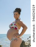 Small photo of Pregnant woman in bikini posing against sea. Attractive expectant mother in swimwear standing arms akimbo looking at camera smiling