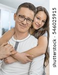 Small photo of Portrait of affectionate girl embracing father from behind at home