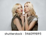 Small photo of Two attractive blonde girls give aery kiss. Natural makeup, red lips and blue eyes.