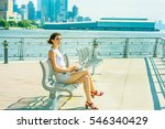 Small photo of American college student studying in New York in summer, wearing white deep v neck crop tank top, shorts, high heel sandals, sitting on chair at park, working on laptop computer. Color filtered effect