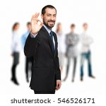 Small photo of Smiling businessman making alright sign in front of a group of business people