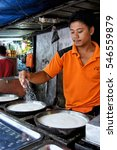 Small photo of KUALA LUMPUR, MALAYSIA-JANUARY 15, 2012: Street hawker sprinkling sugars while preparing griddle pancake (apam balik) made of crispy flour, egg mixture, nuts and sugar.