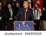 "Small photo of HERSHEY, PA - DECEMBER 15, 2016: President-Elect Donald Trump smiles during a speech at a ""Thank You"" Tour rally held at the Giant Center. The new USA logo with Make America Great Again is visible."