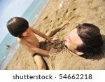 Real happiness, playing on beach: my dad under the sand - stock photo