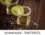 Small photo of Macro photo of shots of gold Mexican tequila with lime and salt on wooden rustic background. Alcoholic drink concept. selective focus.
