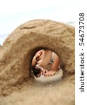 Building a sand tunnel on the beach - stock photo