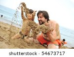 Playing together in sand on beach, young father and a little son - stock photo