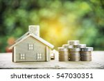 Small photo of coin stack with house model, savings plans for housing ,green background, financial concept