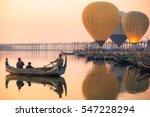 Sunrise at U Bein Bridge with boat and hot air balloon, Mandalay, Myanmar.