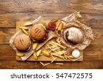 Small photo of Fast food dish top view. Meat burger in craft paper, potato chips and wedges. Take away composition. French fries, hamburger, mayonnaise and ketchup sauces on wood. Menu or receipt background