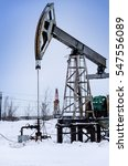 Small photo of Pump jack and wellhead in the oilfield. Rig at the background. Oil and gas concept.