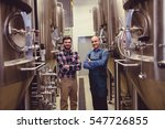 Small photo of Portrait of confident worker and owner standing amidst machinery at brewery