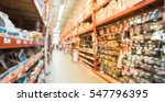 Small photo of Blurred a large hardware store, tools and material. Defocused interior of home improvement retailer, racks of door hardware, weather proofing and lockset floor to ceiling. Customers shopping. Panorama