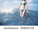 Woman Standing In Waves At Beach