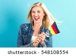 Happy young woman holding German flag on a blue background