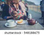 a young mother is breastfeeding ... | Shutterstock . vector #548188675