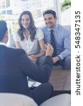 Small photo of Smiling young couple in meeting with a financial adviser at home