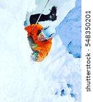 man climbing frozen waterfall. | Shutterstock . vector #548350201