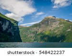 Group of kayakers at Geiranger fjord steep shores. Popular water excursion to waterfalls. Geirangerfjord, Norway. - stock photo