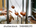 Small photo of Physics experiment with cradle balls in laboratory. Research concept. Conservation of energy. Simple Pendulum, moving towards the main position the potential energy is converted to kinetic energy.