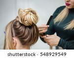 hairdresser makes upper bun... | Shutterstock . vector #548929549