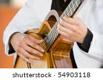 A horizontal photo of a caucasian musician playing a classical guitar at a wedding reception - stock photo