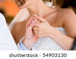 A horizontal photo of a caucasian bride and groom holding hands during a wedding reception - stock photo