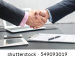 Stock photo close up image of a firm handshake between two colleagues after signing a contract 549093019