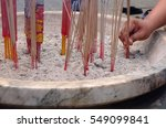 Small photo of Hand is sticking the joss sticks in the pot