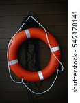 Small photo of Life buoy hanging on wooden wall for emergency response when people sinking to water almost place near pool and beach